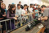 Joel Taylor stokes his Accucraft K-28 with coal as the crowd looks on. Photo by Mike Martin.
