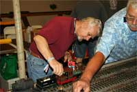 Bill Allen, left, tends to his recently scratch-built 'C.P. Huntington,' as Ron Sickler, right, reaches across the layout to adjust his 'Ruby.' Photo by Rob Lenicheck.