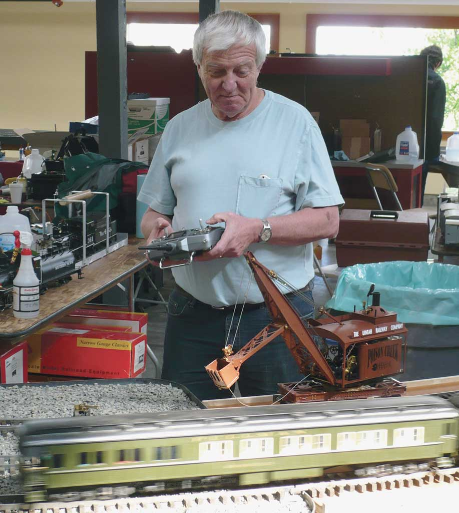 Dan Pantages operates a radio-controlled steam ditcher built by Jim Hadden as a English passenger consist whizzes by.